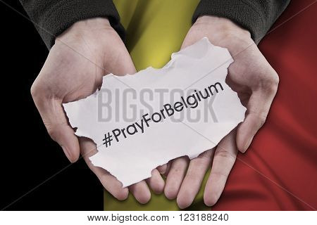 Close up of hands holding a paper piece with a text to pray for Belgium in front of Belgian flag