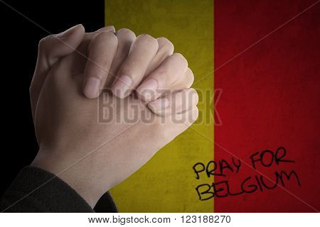 Image of hands posing pray for Brussels with Belgian flag background