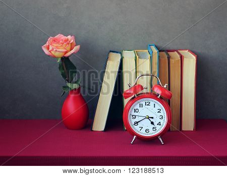 Books with colored covers the rose in red vase and red retro alarm clock on table with tablecloth on a gray background.