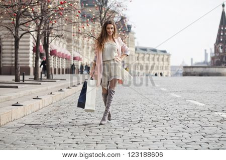 Shopping. Young beautiful brunette woman in beige dress and pink coat