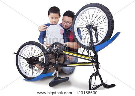 Picture of a little boy and his father using a tool to repair a broken bicycle isolated on white background