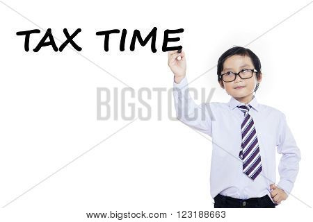 Portrait of cute little student writes tax time on whiteboard to remember the time for paying tax