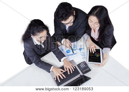 Close up of three multi ethnic businesspeople discussing together in a business meeting using laptop and tablet with financial graph