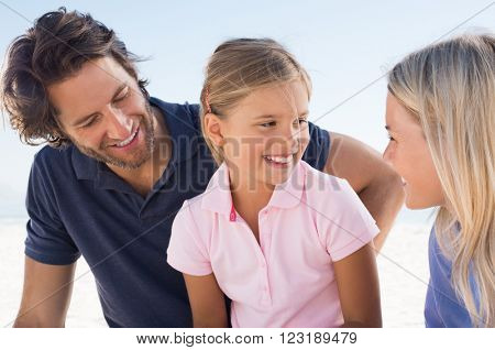 Cute little daughter looking at mother with a smile. Family enjoying holiday at beach. Little girl in conversation with her parents outdoor.