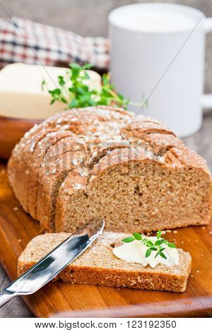 Sliced Irish stoneground soda bread with butter and thyme on the wooden table