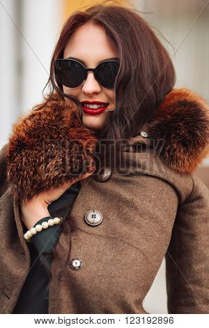 fashion Outdoors Sexy glamor young woman with chic long dark hair beautiful young brunette girl wearing stylish sunglasses, trendy blue dress, luxurious fur coats and gloves fashion makeup posing in autumn park