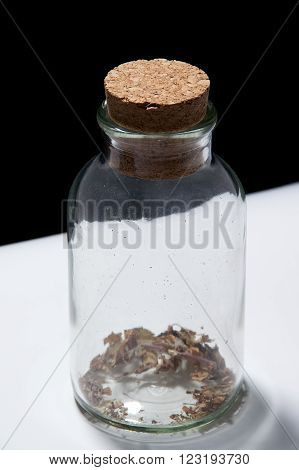 Old glass bottle with cork stopper on white against black background with some herbs remaining in the bottom.