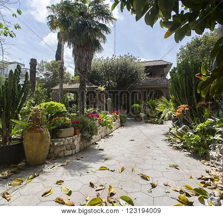 LECCE ITALY -April 19 2015.Yard urban villa surrounded by flowers and plants.