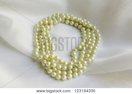 Pearl Necklace on delicate White silk background