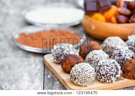 Assorted dark chocolate truffles with cocoa powder sesame seeds and cup of Cappuccino
