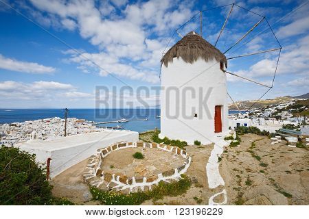 Old traditional windmill and town of Mykonos in Cyclades, Greece.