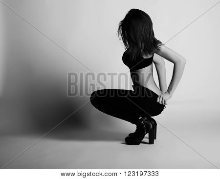 Black and white photo of beautiful brunette woman model  posing in studio. Wearing jeans, bra and heels