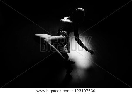 Brunette sexy slim woman laying dancing on floor, indoors, black and white