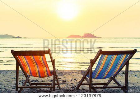 Two deckchairs on a sunny sea beach.