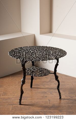 wrought-iron table brown on the floor in the corner of the room