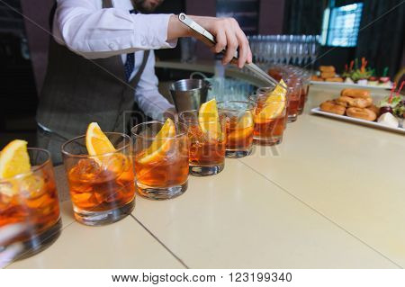 Bartender, barman preparing an alcoholic beverage, drink in nightclub, pub or bar. Man lays in a glass of whiskey with ice and slices of orange. glasses of whiskey or rum lined up.