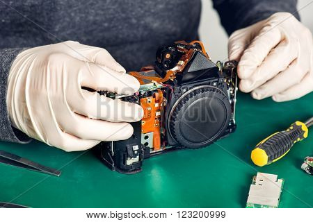 Close up of hands in latex gloves holding digital camera without front and back panels