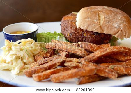 Vegetable burger served with sweet potato fries