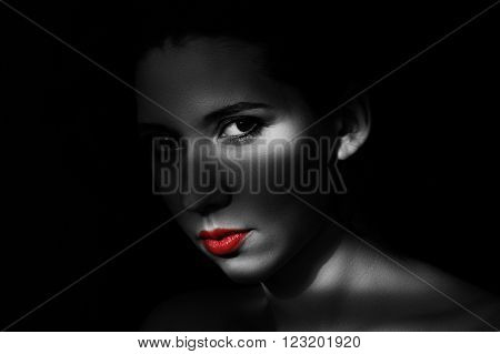 Artistic beauty portrait of young woman with creative lighting effect. Fashion close up black and white photo of girl face with red lips in low key.