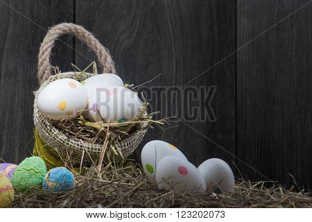 Basket with Easter eggs and easter cake isolated on wooden background
