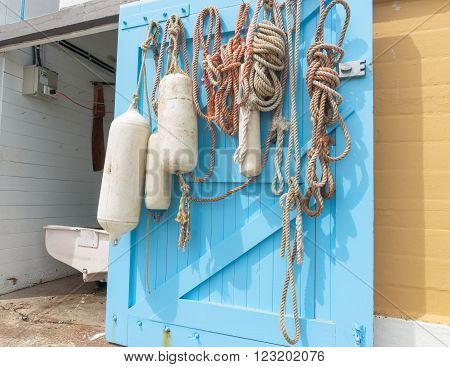 Hanks of rope and buoys hanging on inside open blue boat shed door with dinghy stern in opening