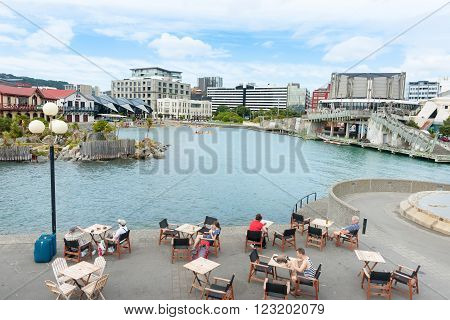 Wellington, Nerw Zealand - February 15, 2016; Enjoying the waterside outdoors Wellington New Zealand people sitting around tables beside harbour inlet with city buildings across water.
