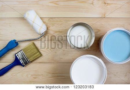 paint roller brush and a white and blue paint on wooden boards in banks