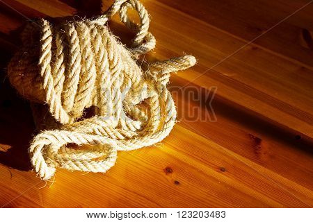 Vintage toned image of hank large ship's rope on the background of a brown wooden table. Frame made of rope.