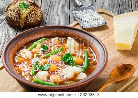 Minestrone vegetable soup with beans cauliflower tomatoes close-up top view