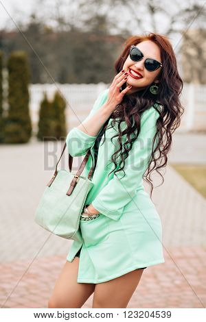 Sunny positive portrait of sexy stunning girl in short bight dress  having fun on the street, joy, happiness, weekends, bright colors.