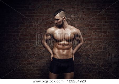 Young muscular man posing near red brick wall