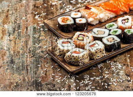 Sushi maki sashimi and sushi rolls on rustic wooden background