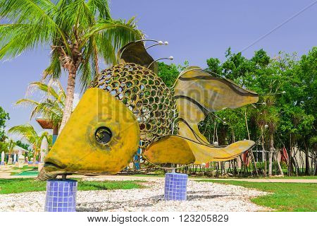 Cayo Coco island, Melia jardines del rey,Cuba, Sep 2, 2015 giant big, decorative beautiful fish made of metal  shits and horseshoe parts, standing on ceramic tile posts in cozy tropical garden