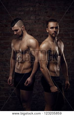 Young muscular men near red brick wall