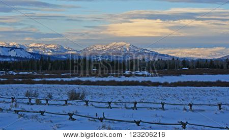 Grand Tetons at sunset with split rail fence in foreground in Grand Tetons National Park in Wyoming USA