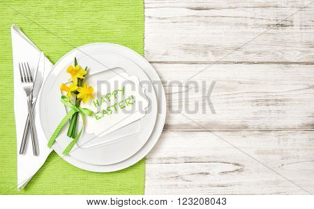 Spring table decoration with narcissus flowers. Greetingds card Happy Easter!
