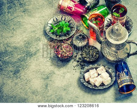 Tea table place setting with colorful glasses. Vintage style toned picture