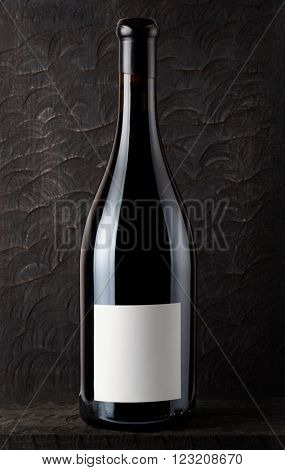 Bottle of Shiraz red wine, old wooden surface in background