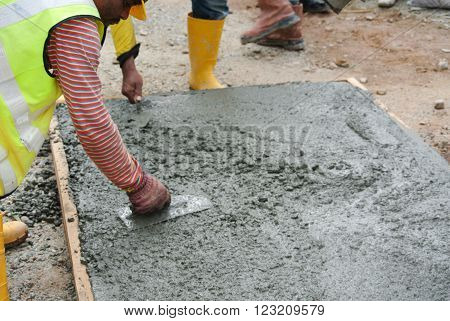 JOHOR, MALAYSIA -OCTOBER 20, 2015: Construction workers leveling the pouring wet concrete on floor at the construction site.