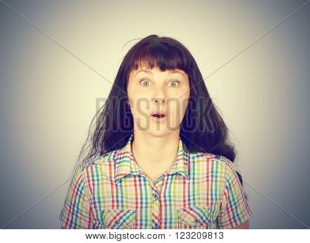 Surprise astonished woman.  woman looking surprised in full disbelief wide open mouth isolated grey wall background