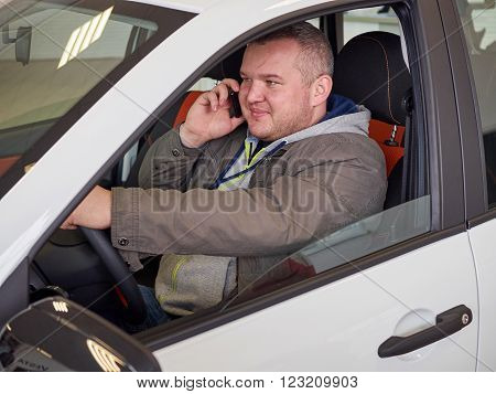 Young fat man behind wheel talking on phone