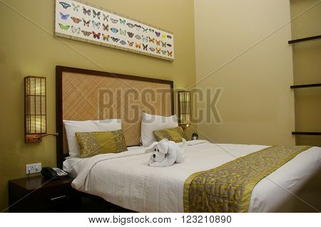 CLUB MAHINDRA RESORT, VIRAJPET, KARNATKA/INDIA MAR 13:  King sized bed in Club Mahindra resort studio accommodation decorated with beautiful puppy towel art and butter fly theme head board Mar 13, 2016 in Virajpet,Karnataka,India.