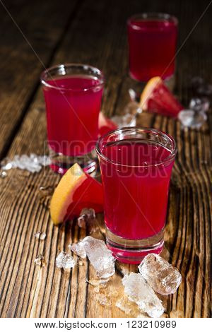 Shot Glass with Grapefruit Liqueur on rustic wooden background