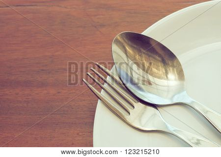 dishware set on wood table with plate spoon and fork image used filter vintage