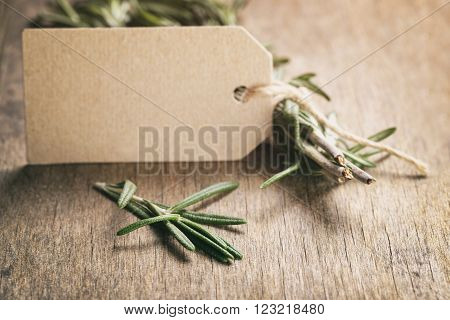 rosemary with paper card on wood table, vintage toned