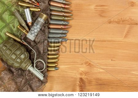 Different types of ammunition on a wooden background. Grenade and bullets. Arms trade.