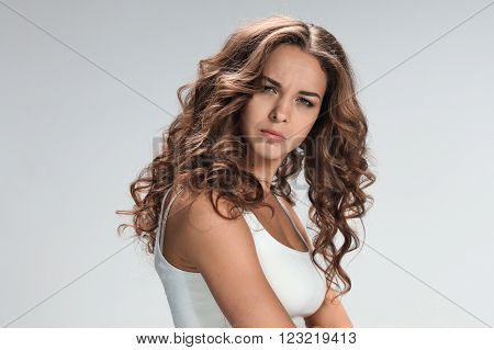 The young woman's portrait with sad emotions on gray background