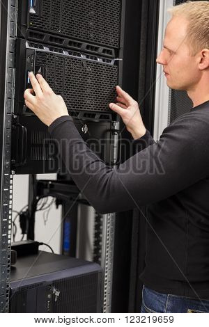 It engineer or technician work with servers in data rack. Shot in a large enterprise datacenter.