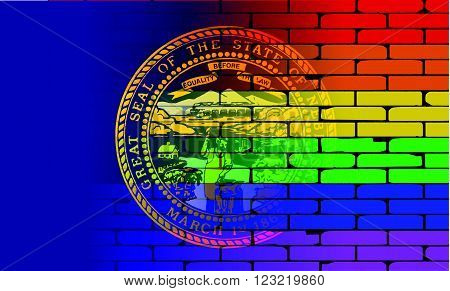 A well worn wall painted with a LGBT rainbow with the Nebraska state flag