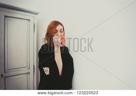 Young Redhead Woman Drinking With Orange Mug